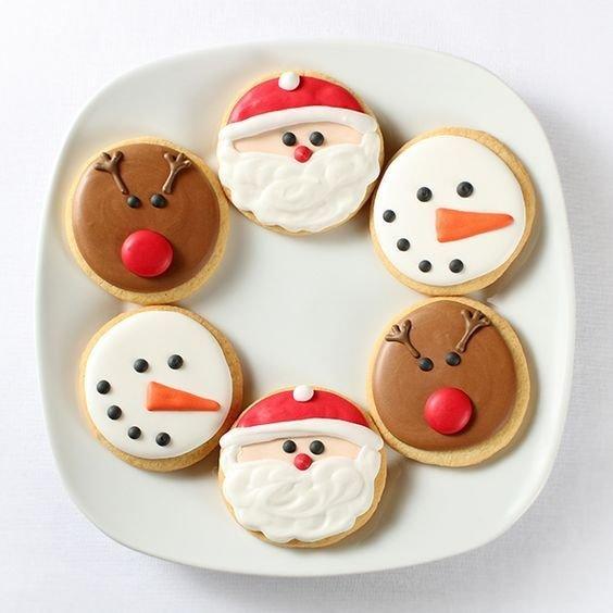 Un piatto bianco quadrato con sopra sei biscotti rotondi a tema natalizio. Glassa a forma di Babbo Natale, renna e pupazzo di neve.