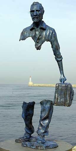 Scultura di un uomo con una valigia in mano. La scultura presenta solo parte delle gambe e dei piedi e la parte superiore del tronco con la testa e un braccio che regge una valigia. L'installazione è sul mare e attraverso la scultura si vede, in lontananza una diga con un faro.