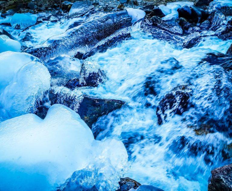 acqua impetuosa con ghiaccio che scorre sopra delle rocce