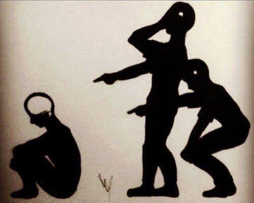 Tre immagini scure su sfondo marrone. Un ragazzo seduto di spalle e due ragazzi in piedi con l'indice puntato che lo deridono. Lo spazio del cervello nel ragazzo seduto è di dimensioni normali disegnato in bianco, mentre negli altri due ragazzi in piedi è di dimensioni piccolissime.