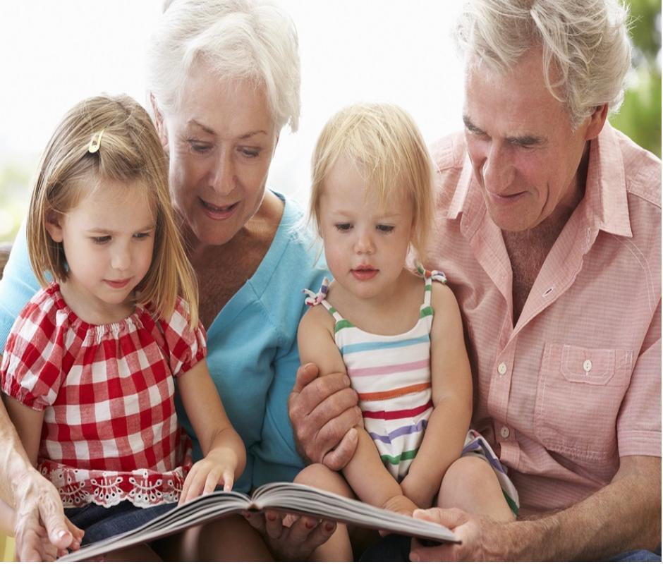 coppia di nonni che leggono un libro ai due nipotini